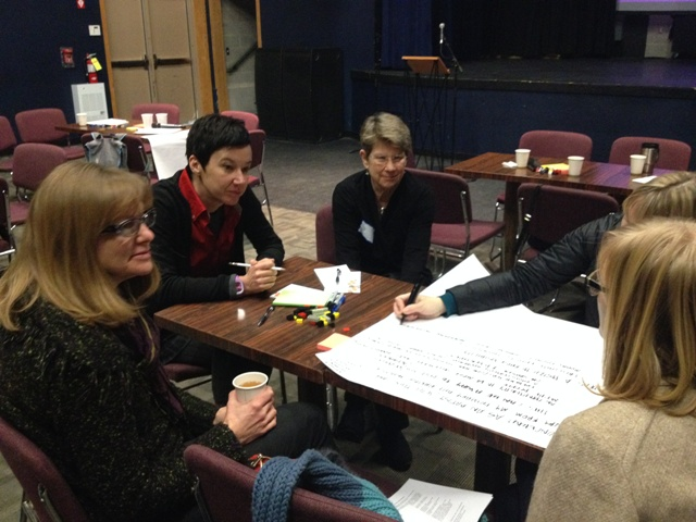 Ann Markusen (centre) chats with participants as they work on their great urban ideas